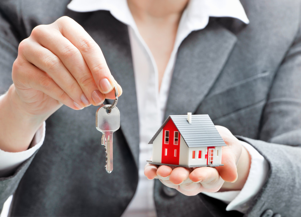 woman holding a house and keys